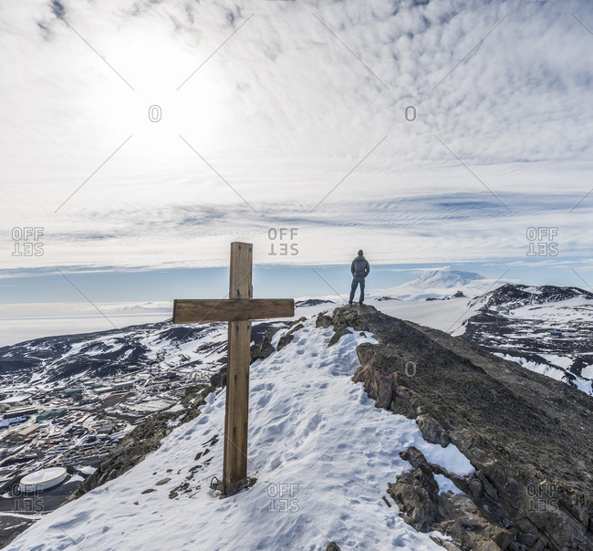 A man stand on top of Observation Hill above McMurdo Station, with the memorial to Robert Falcon Scott in the foreground.