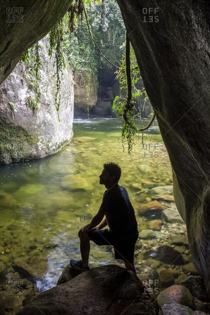 Man sitting in cave in rainforest, Serra Dos Orgaos National Park, Rio de Janeiro State, Brazil