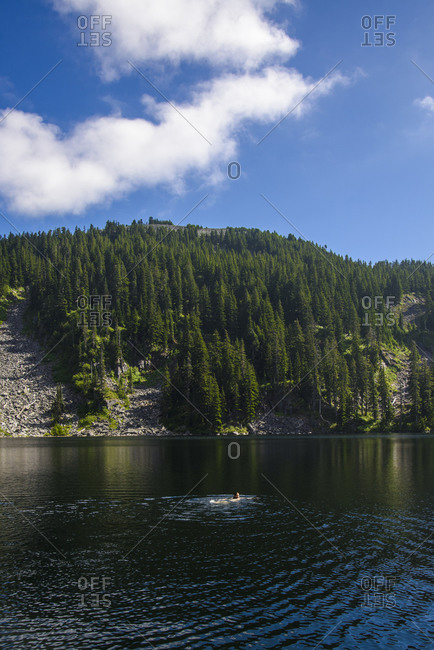 A man swims in an alpine lake in the Cascade Mountains