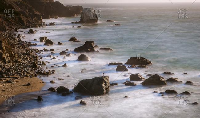 a small figure stands on coastal rocks