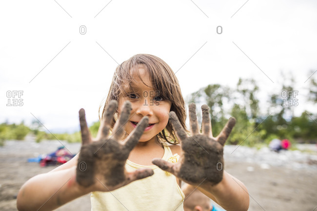 Girl showing dirty hands with mud
