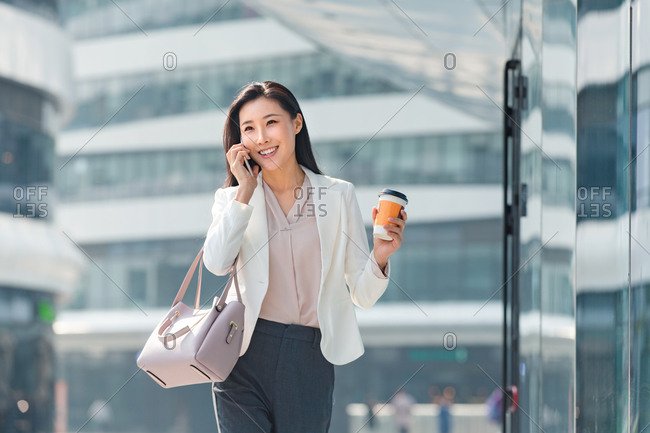 Young business woman walking while on a call