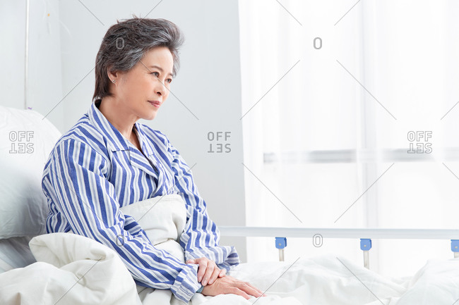 Elderly patient sitting in a hospital bed