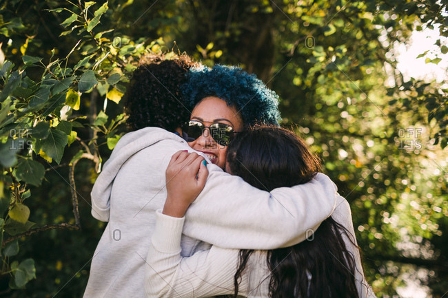 Loving children embracing mother with blue hair against trees in park