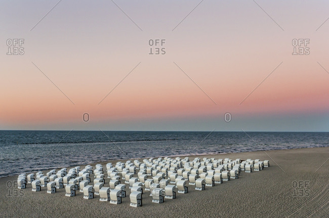 Hooded chairs at beach against sky during sunset- Ruegen- Germany