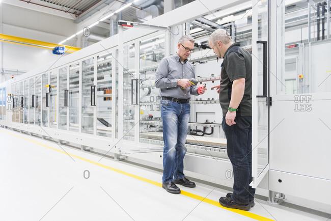 Two men talking in a factory