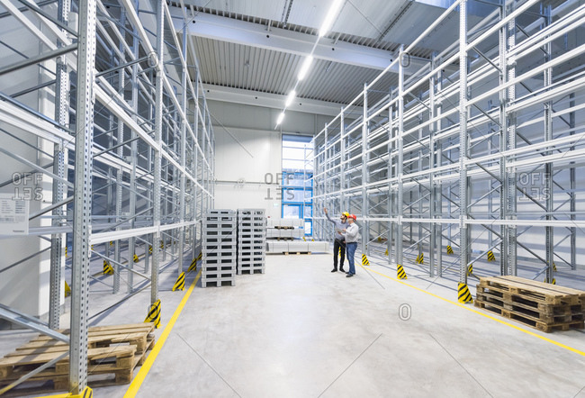 Two men wearing hard hats talking in storehouse of a factory