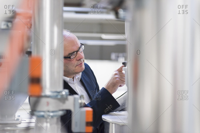 Businessman examining a machine in a factory
