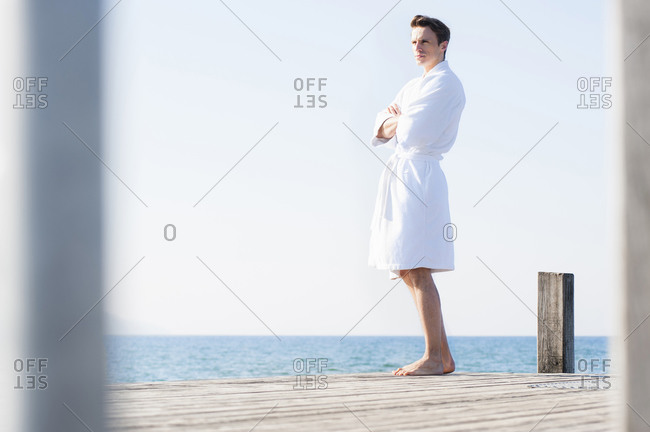 Handsome mid adult man wearing bathrobe standing on pier over sea against clear sky