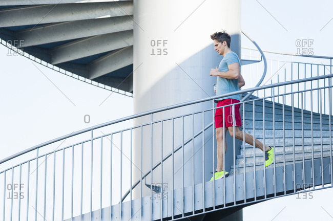 Man running on spiral staircase in city