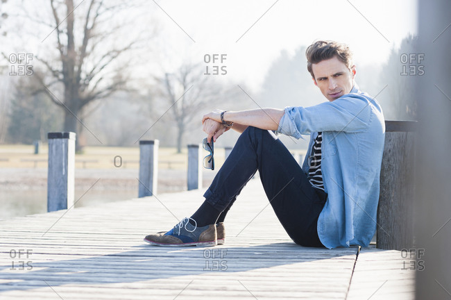 Thoughtful handsome mid adult man looking away while sitting on pier