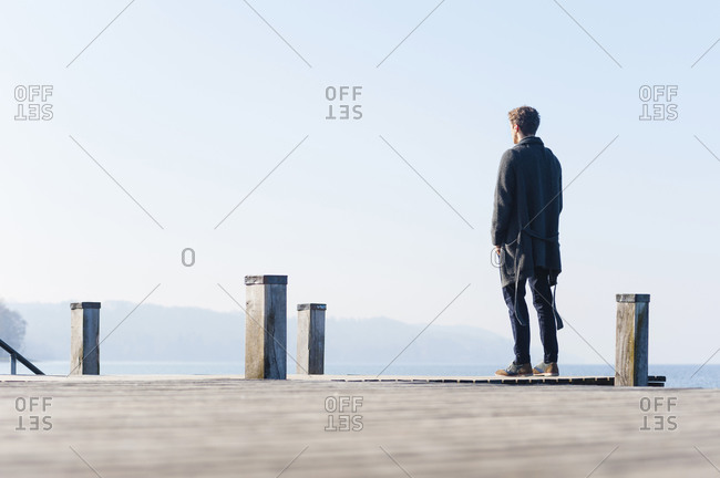 Man looking at lake against clear sky while standing on pier during sunny day