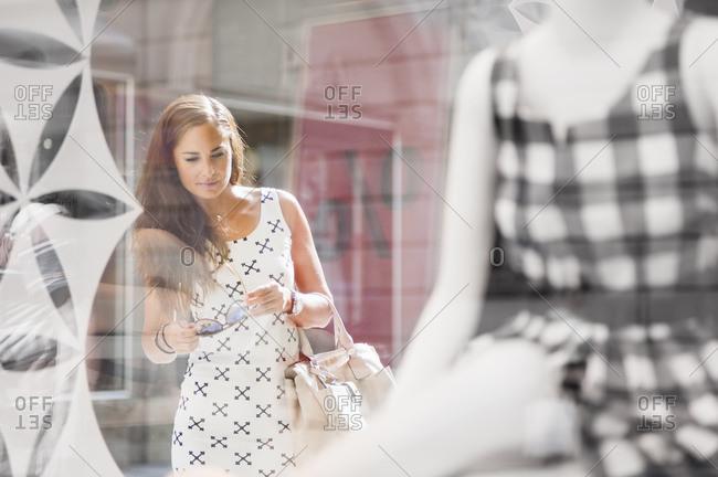 Portrait of woman on a shopping spree looking in shop window
