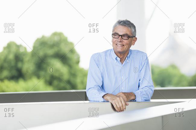Portrait of successful senior businessman leaning on railing