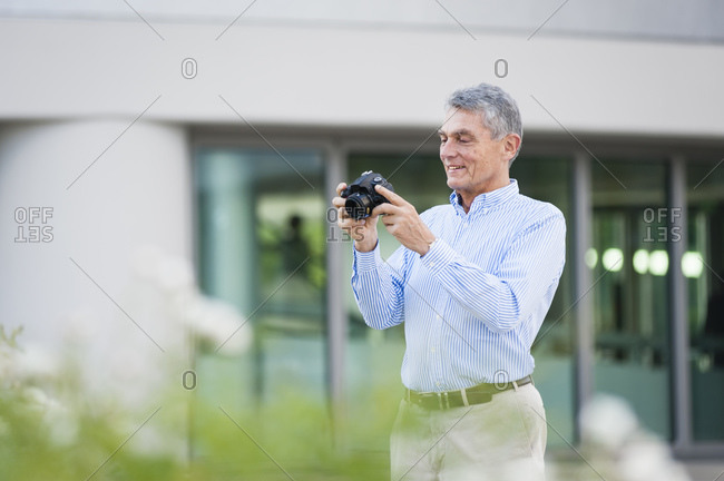 Portrait of smiling senior businessman with digital camera outdoors