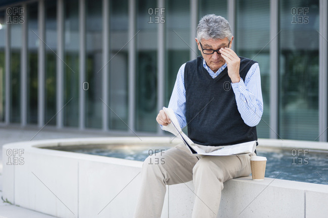 Senior businessman with coffee to go reading newspaper outdoors