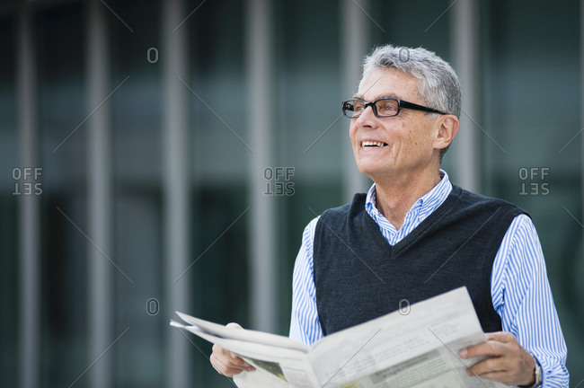 Portrait of smiling senior businessman with newspaper outdoors