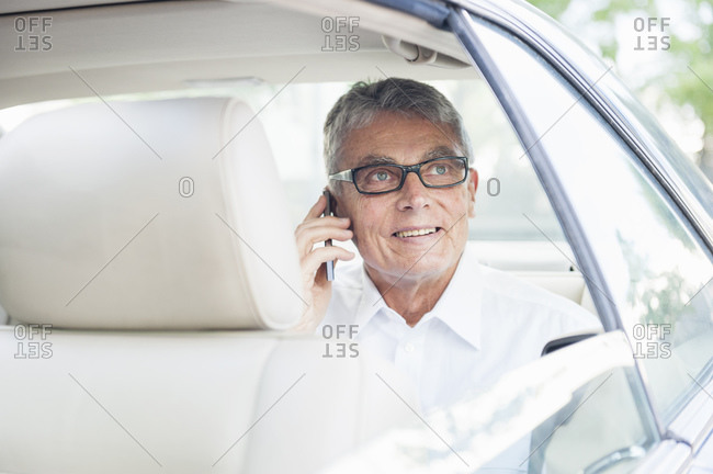 Portrait of smiling senior businessman on the phone looking out of car window car