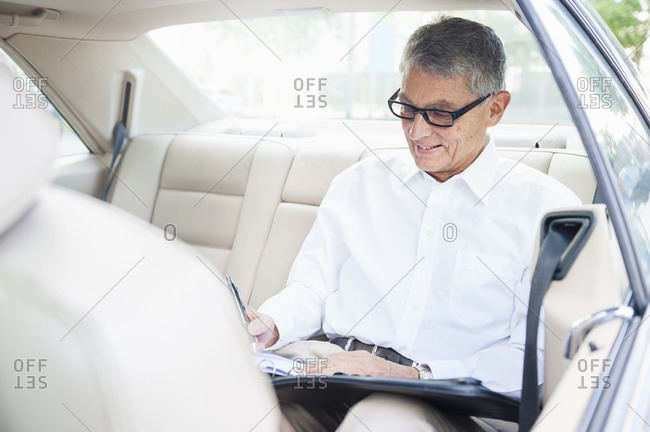 Smiling senior businessman working on back seat of car