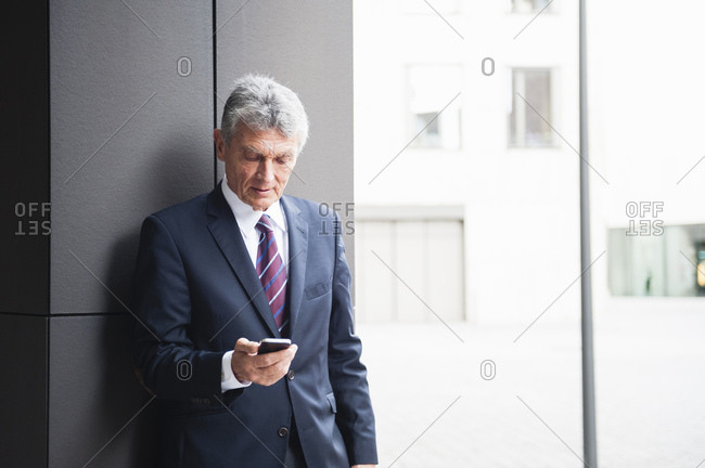 Portrait of senior businessman looking at cell phone outdoors
