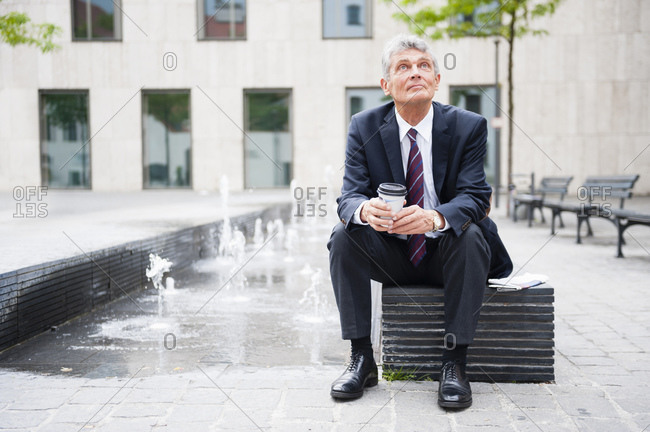Portrait of senior businessman having a break with coffee to go outdoors