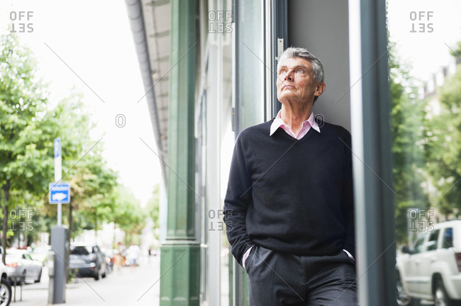 Portrait of serious senior businessman outdoors looking up