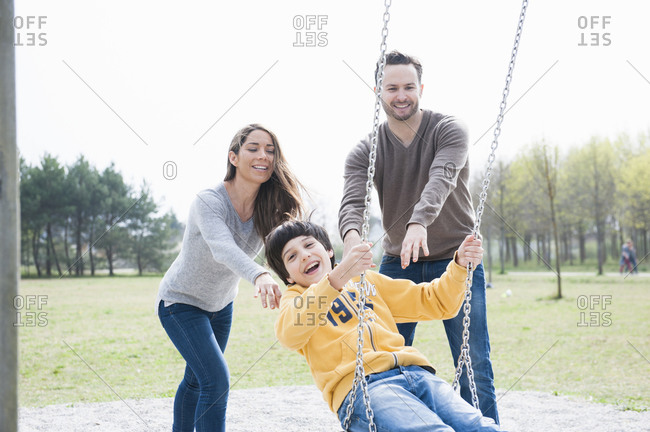 Happy parents pushing son on swing at park against clear sky