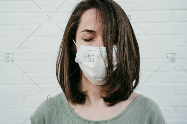 Portrait of woman with eyes closed wearing protective mask