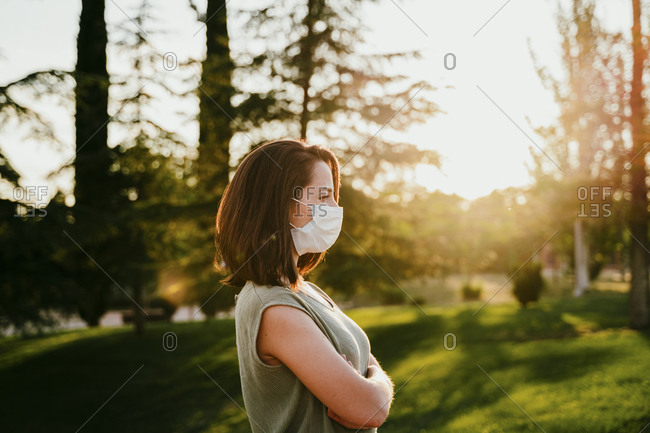 Pensive woman wearing protective mask in nature