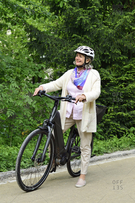 Happy senior woman standing with electric bicycle on footpath in park