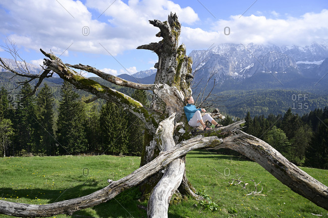 Woman relaxing on dead tree against mountains during sunny day