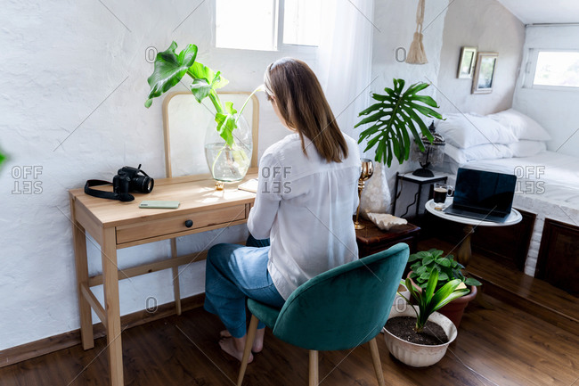 Woman with long brown hair sitting on chair at desk in bedroom