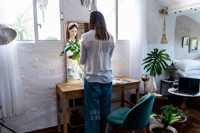 Woman arranging plants in vase while standing at home