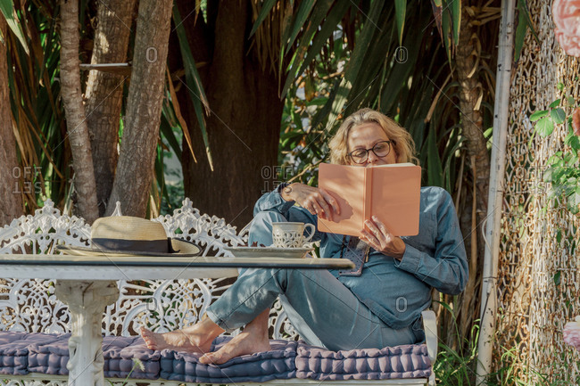 Senior woman sitting on garden bench reading a book