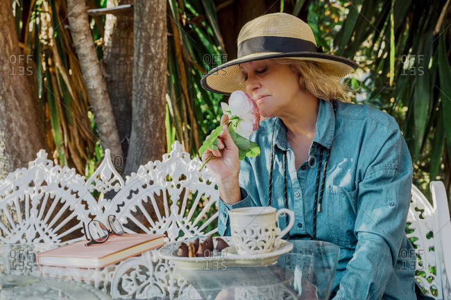 Portrait of senior woman sitting on garden bench smelling at rose blossom