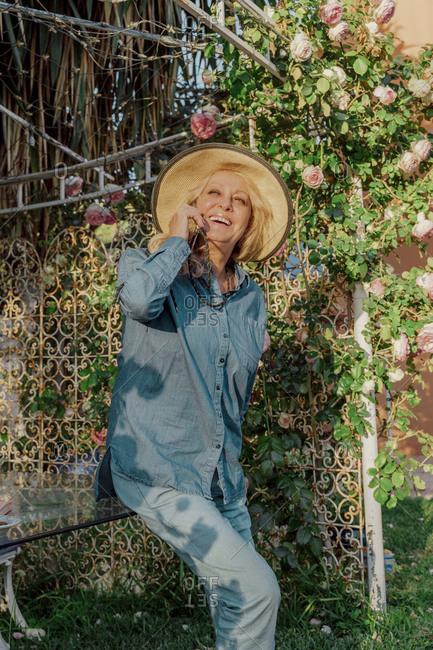 Portrait of happy senior woman on the phone in garden