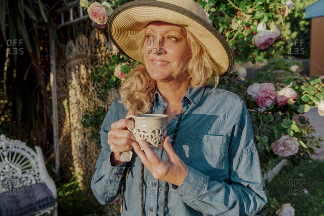 Portrait of smiling senior woman with cup of tea in her garden