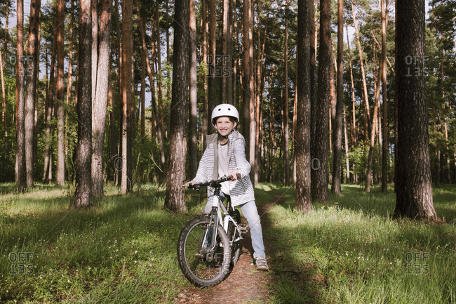 Happy boy with bicycle in forest