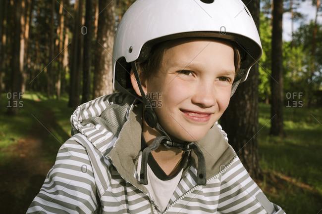 Happy boy wearing cycling helmet in forest