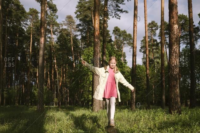 Girl walking on log in forest