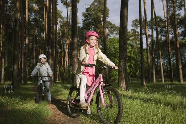 Girl and boy riding bicycles on footpath in forest