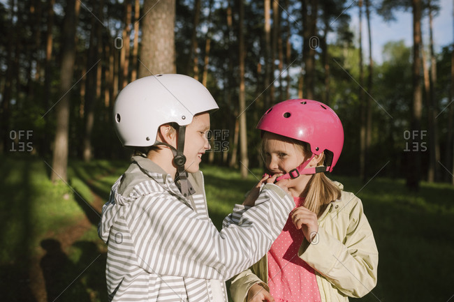 Happy boy fastening cycling helmet for girl in forest