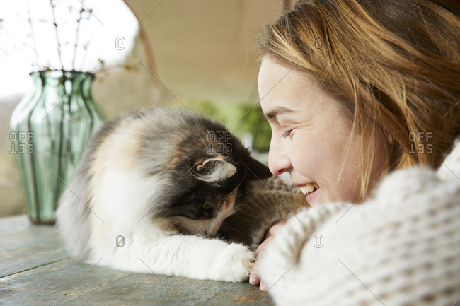 Happy woman with Norwegian forest cat on wooden table outdoors