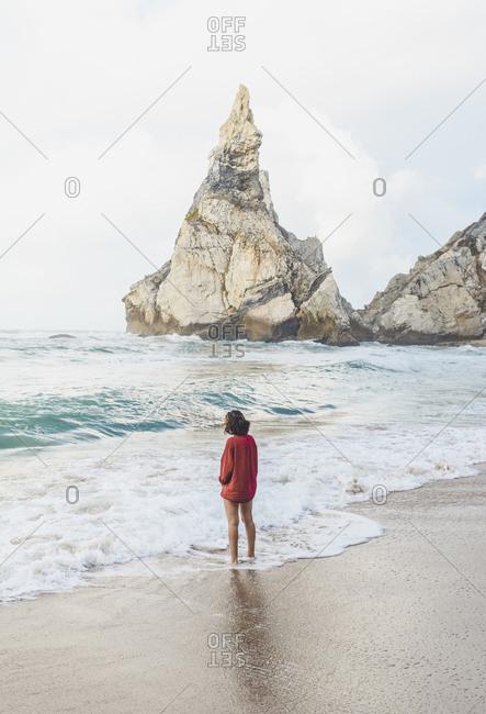 Young woman standing on shore at Praia da Ursa- Lisboa- Portugal