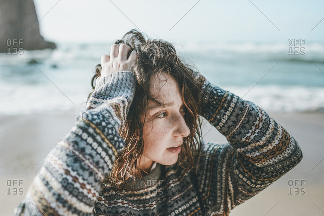 Young woman with hands in hair looking away while standing at Praia da Ursa- Lisboa- Portugal