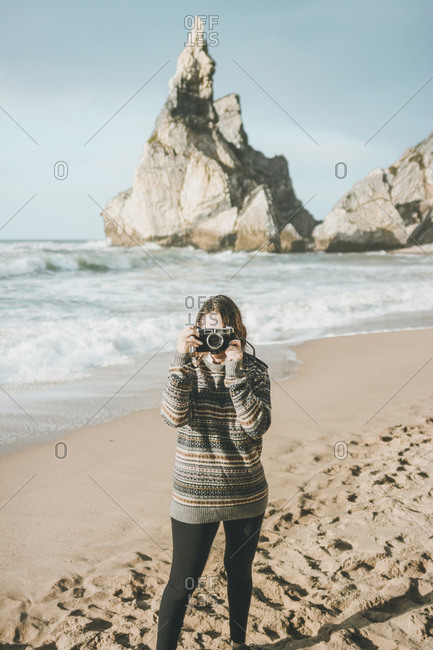 Young woman photographing while standing against rock formation at beach- Praia da Ursa- Lisboa- Portugal