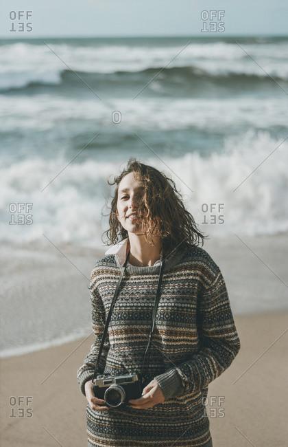 Beautiful young woman standing with camera at beach- Praia da Ursa- Lisboa- Portugal