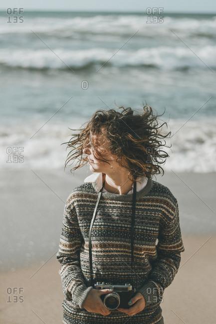 Young woman standing with tousled hair against sea- Praia da Ursa- Lisboa- Portugal