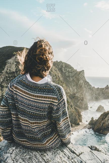 Young woman sitting on rock while looking at beach- Praia da Ursa- Lisboa- Portugal