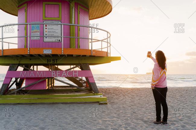 Woman photographing lifeguard hut at Miami beach during sunrise- Florida- USA